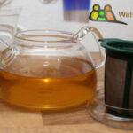 Frisch aufgebrühter Tee in einer Glaskanne, Sieb.
