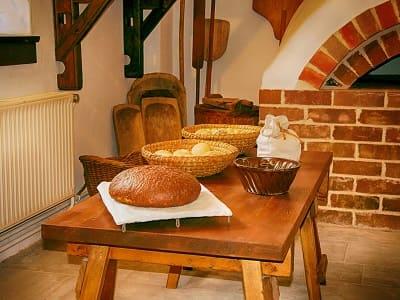 Traditionelle Backstube mit einem Tisch mit Broten bestückt und Backschaufeln im Hintergrund. Gemütliche Bäckerei mit Backschaufel.